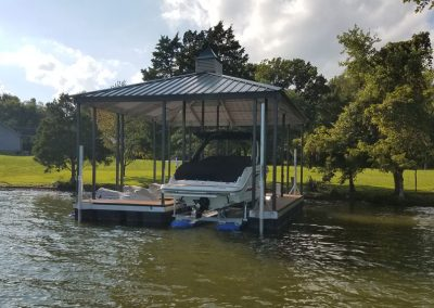 An aluminum wahoo dock with a blue roof and a covered boat parked under it with a gangway leading to a grassy field and large trees