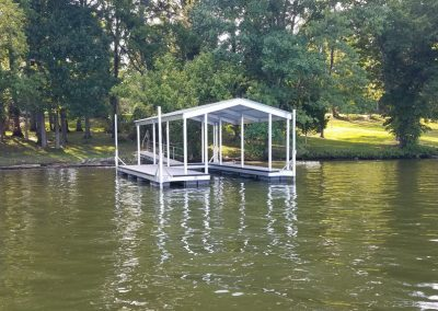 An aluminum wahoo dock with a white roof and a gangway leading to a grassy field and large trees