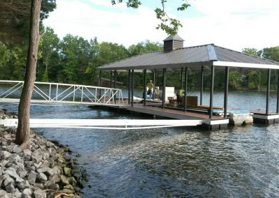 An aluminum wahoo dock with a black roof and a gangway leading up to a rocky shore and a shoreline with big green trees in the background
