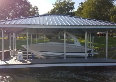 An aluminum wahoo boat dock with a large white boat parked under a roof and a grassy yard with a house in the background