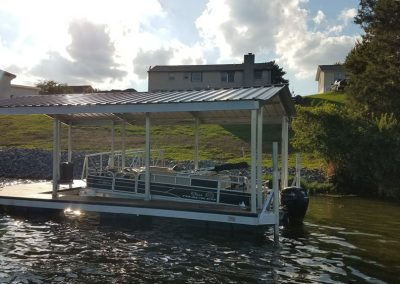 An aluminum wahoo boat dock with a roof and a pontoon boat parked under it and a gangway leading to a rocky shore and a hill with a house