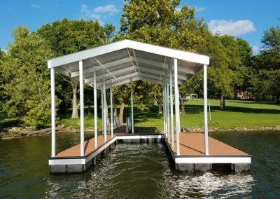 An aluminum wahoo boat dock with a roof and a gangway leading to a big grassy yard full of large green trees