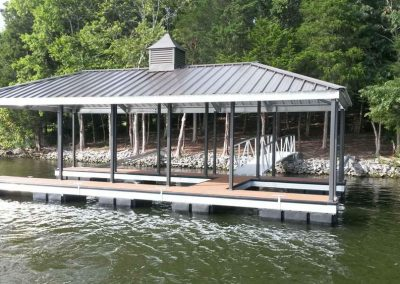 An aluminum wahoo dock with a black roof and a gangway leading up to a rocky shore and hill with big green trees