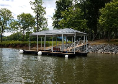 An aluminum wahoo dock with a roof and a gangway leading up a rocky bank to a field of big green trees