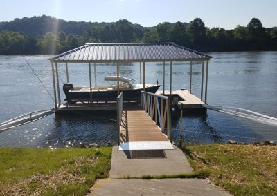 A gangway leading to an aluminum wahoo boat dock with a dark roof and a boat parked under it on a river with trees across the way