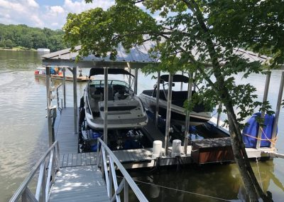 A gangway leading to an aluminum wahoo boat dock with a roof and two boast parked under it with trees in the background across the river