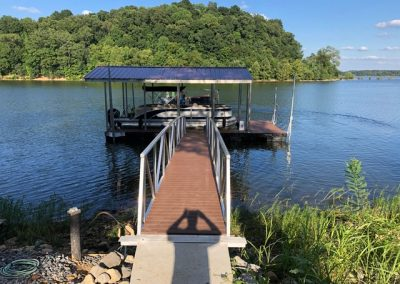 An aluminum wahoo gangway leading to a boat dock with a roof on a river and a pontoon parked under it