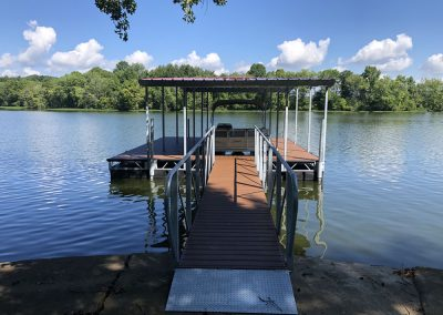 A gangway leading to a Box Truss Steel dock with red roof and pontoon boat parked under it on river with trees in background