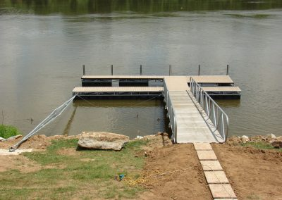 A stone path leading to a gangway leading to a box truss steel dock on a river with trees in the background