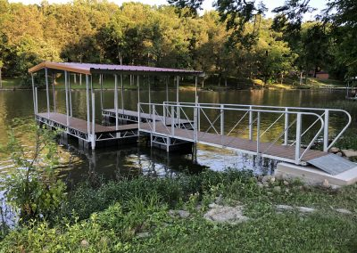 A gangway leading to a Box Truss Steel dock with red roof on river with trees in background