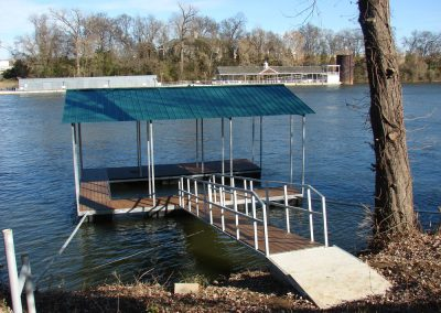 A gangway leading to a galvanized steel boat dock with a blue roof on a river with a house and trees in the background