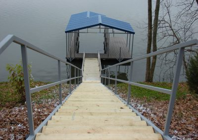 Stairs leading down a hill to a gangway and a galvanized steel boat dock with a blue roof on a river