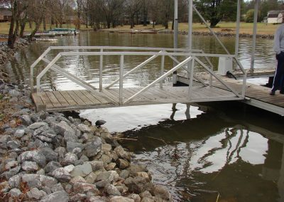 A gangway leading from a rocky shoreline to a galvanized steel boat dock on a river