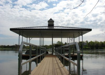 A gangway leading to a galvanized steel boat dock with a black roof and jet-ski and boat parked under it