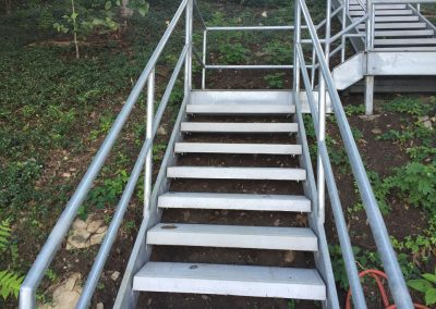 A close up of galvanized steel stairs with railing going up a grassy hill to a landing