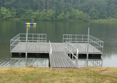 A large rectangular galvanized steel dock on a river with big green trees on the shore in the background