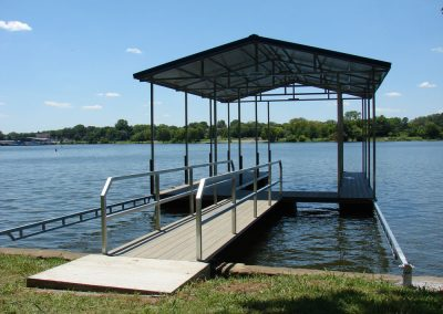 A gangway leading to a galvanized steel boat dock with a roof on a river with big green trees along the shoreline