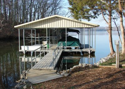 A gangway leading to a galvanized steel boat dock with a roof on a river with a covered boat parked under it
