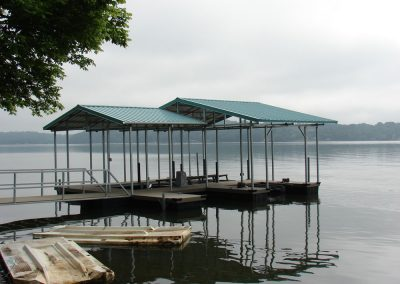 A gangway leading to a galvanized steel boat dock with a roof on a river with trees in the background