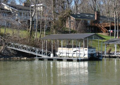 A gangway leading from a backyard to a galvanized steel boat dock with a roof on a river with a pontoon boat parked under it