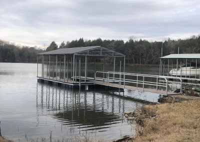 A gangway leading to a galvanized steel boat dock with a roof on a river with bare trees in the background