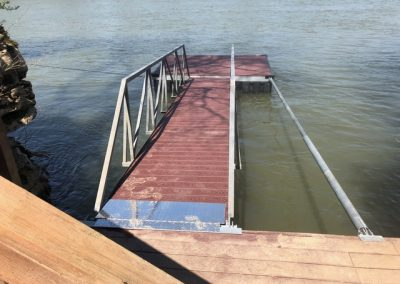 A wooden dock leading to a galvanized steel boat dock on a river