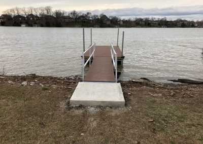 A galvanized steel gangway leading to a boat dock on a river with trees in the background