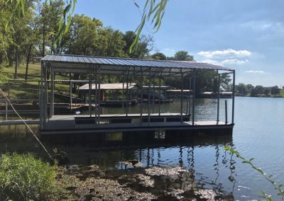 A galvanized steel boat dock with a roof on a river with big green trees along the shoreline