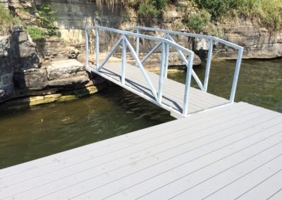 A galvanized steel boat dock on a river with a gangway leading to a rock wall