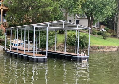A galvanized steel boat dock with a roof on a river with a gangway leading up to a backyard