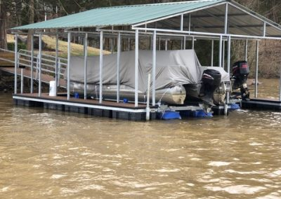 A boat dock with a roof on a river with a pontoon boat parked and covered and a gangway leading up to a yard