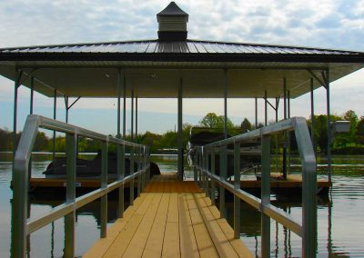 A gangway leading to a Galvanized Steel boat dock with a pitched black roof on river with trees in background