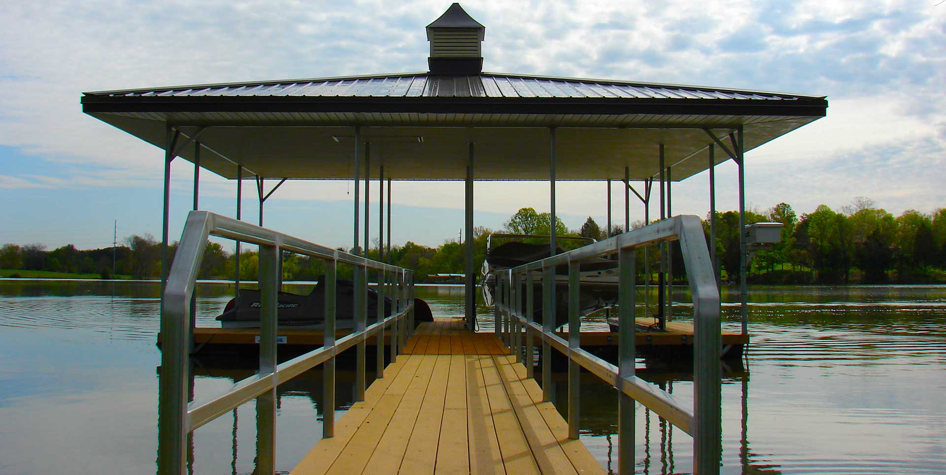 Galvanized Steel boat dock with gangway on river with trees in background