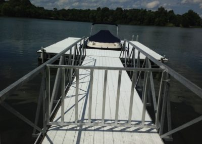 A henn gate on a gangway leading to a dock with a boat parked in the middle