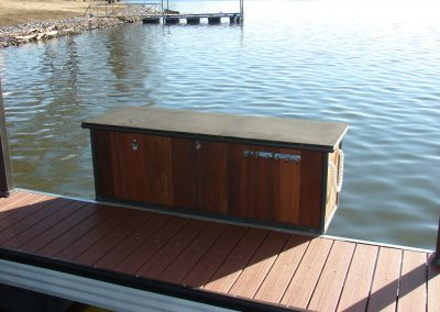 An IPE wooden deck box with a rope handle mounted to the side of a wood topped deck