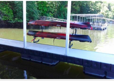 A kayak rack mounted to the side of a dock with two red kayaks hanging on it