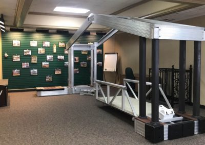 Showroom aluminum dock with roof sample with floor samples and green wall with photos behind it