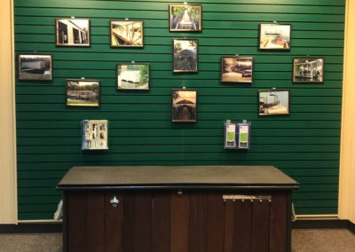 A showroom with a green wall covered with framed photos of aluminum docks and a wood island in front of the wall
