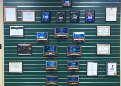 Green showroom wall covered with awards on plaques and framed accolades
