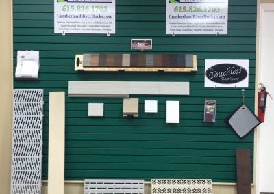 Green showroom wall with Cumberland River signs and samples of dock materials