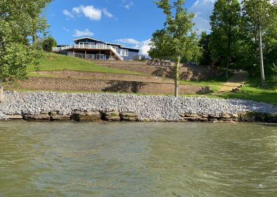 Rip rap erosion control rocks along a shoreline with a field and house in the background and river in the foreground