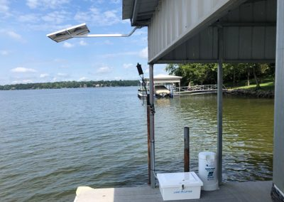 A solar panel mounted off of the metal roof of a boat dock