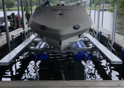 A white boat with a white cover on it sitting on a blue boat lift surrounded by docks
