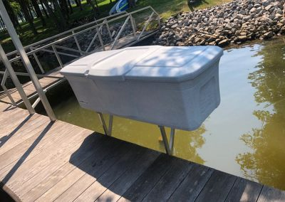 A large white waterproof storage box mounted on the side of a wooden dock