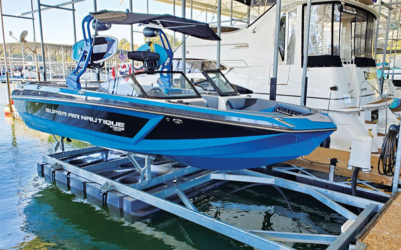 blue boat on front mount boat lift in dock