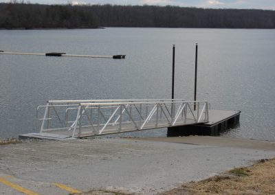 An aluminum gangway leading to a floating dock next to a boat ramp on a lake with bare trees in the background