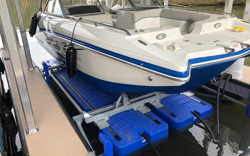 Boat on blue lift in shallow water dock