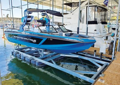A blue ski boat sitting out of the water on top of a front mount boat lift in a marina surrounded by other boats