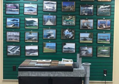 Green showroom wall covered with photos of galvanized steel docks framed in black frames with a table and sample materials in front