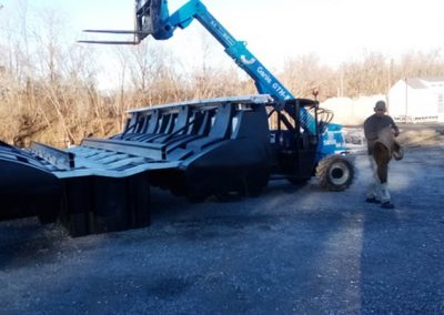 A HarborHoist boat lift being moved in a gravel lot with a man standing next to it and bare trees behind it